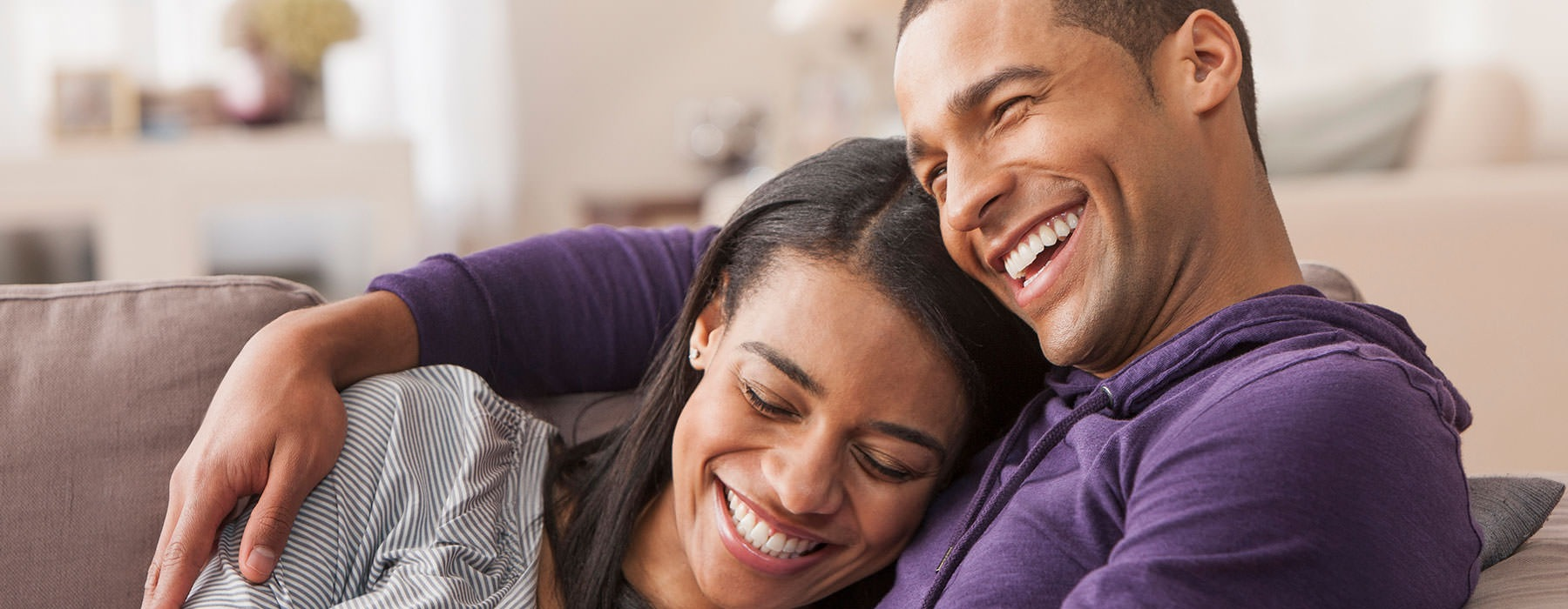 a lifestyle image of a couple holding each other and smiling