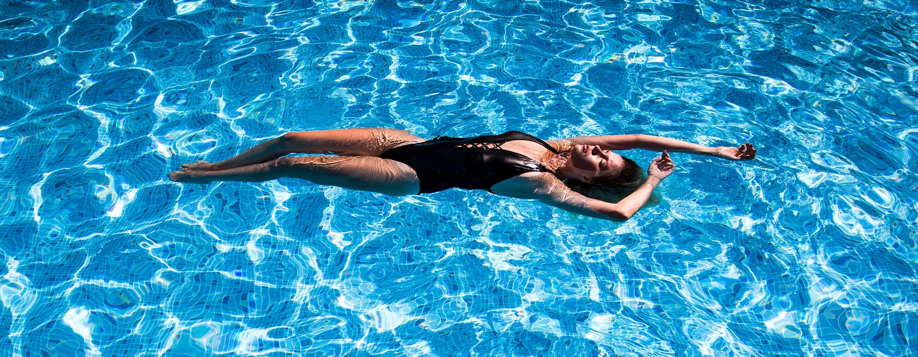 a lifestyle image of a woman sunbathing in the middle of a bright swimming pool